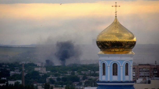 FILE - This July 14, 2014 file photo shows black smoke billowing following a mortar attack during fighting between Ukrainian government troops and pro-Russian fighters in Luhansk, Ukraine. (AP Photo, Yuri Snegirev, Rossiyiskaya Gazeta, File)