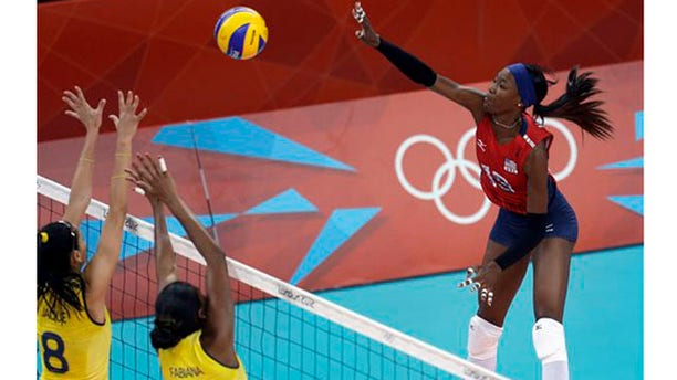 July 30, 2012: United States Destinee Hooker, right, spikes the ball over Brazil's Jaqueline Carvalho (8) and Fabiana Claudino (1) during a women's preliminary volleyball match at the 2012 Summer Olympics on Monday, in London.