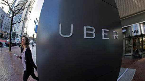 In this photo taken Tuesday, Dec. 16, 2014, a woman leaves the headquarters of Uber in San Francisco.