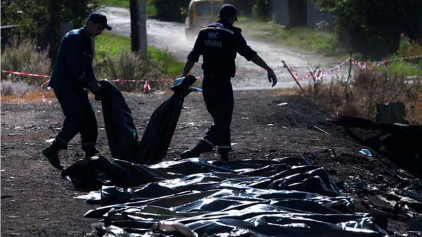 July 21, 2014: Ukrainian Emergency workers carry a victim's body in a plastic bag as other bodies are laid on the ground nearby at the crash site of Malaysia Airlines Flight 17 near the village of Hrabove. (AP Photo/Dmitry Lovetsky)
