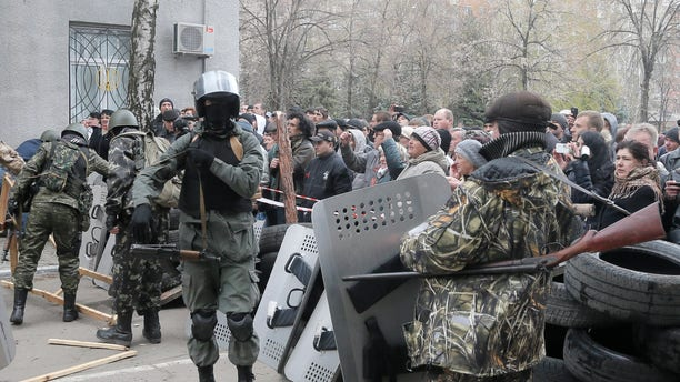 April 12, 2014: Armed pro-Russian activists occupy the police station carrying riot shields as people watch on, in the eastern Ukraine town of Slovyansk.