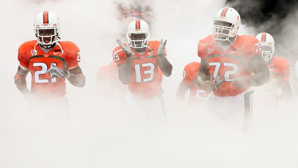CORAL GABLES, FL - OCTOBER 13:  Derron Thomas #21, Ryan Hill #13 and Andrew Bain of the Miami Hurricanes run out of the tunnel prior to taking on the Georgia Tech Yellow Jackets at the Orange Bowl on October 13, 2007 in Coral Gables, Florida.  (Photo by Doug Benc/Getty Images) *** Local Caption *** Derron Thomas;Ryan Hill;Andrew Bain