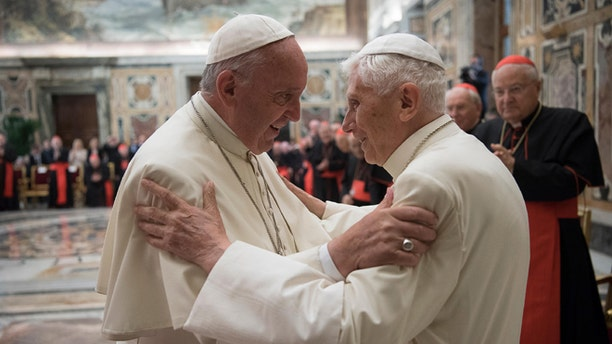 Pope Francis, left, and retired Pope Benedict XVI embrace during a ceremony to celebrate Benedict's 65th anniversary of his ordination as a priest, in the Clementine Hall of the Apostolic Palace, at the Vatican, Tuesday, June 28, 2016. The ceremony served in part to show continuity from Benedict to Francis amid continued nostalgia from some conservatives for Benedictâs tradition-minded papacy. (L'Osservatore Romano/Pool photo via AP)