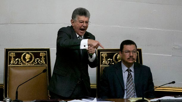 """Congressional President Henry Ramos Allup, left center, gives a speech during a special session of Congress in Caracas, Venezuela, Tuesday, Oct. 25, 2016. After the government suspended a recall referendum seeking the president's removal last week, the opposition-controlled congress began debating Venezuelan President Nicolas Maduro's """"constitutional situation."""" Lawmakers vow to present evidence that he's a dual Colombian citizen and therefore constitutionally ineligible to hold Venezuela's highest office. (AP Photo/Alejandro Cegarra)"""