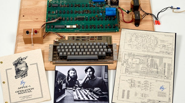 """This undated photo provided by Christie's Auction House shows an """"Apple 1"""" prototype computer, built in 1976, accompanied by an operation manual and schematic as well as a photo of its inventors, Steve Wozniak, left, and Steve Jobs."""