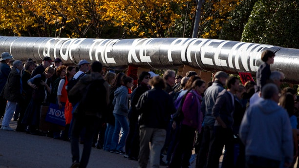 Nov. 6, 2011: Demonstrators march with a replica of a pipeline during a protest outside the White House to demand a stop to the Keystone XL oil pipeline.