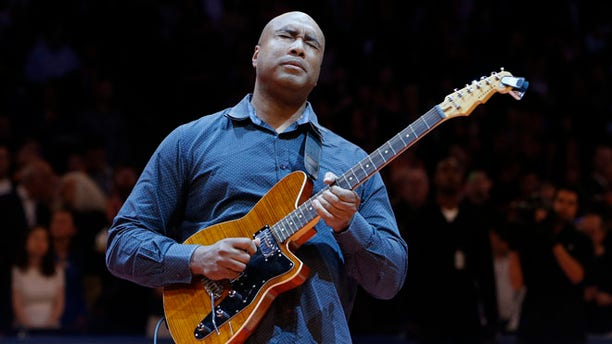 In this Feb. 1, 2014, file photo, former New York Yankee baseball player Bernie Williams plays the nation anthem on a guitar before an NBA basketball game between the Miami Heat and the New York Knicks, in New York.