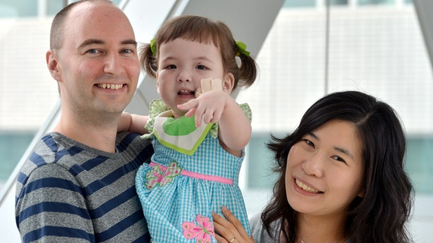 Hannah Warren, 2, poses with her parents Lee Young-mi and Darryl Warren at Seoul National University Hospital in Seoul, South Korea. Hannah received a new windpipe made from her own stem cells in a landmark operation on April 9, 2013, at Children's Hospital of Illinois in Peoria, Ill.
