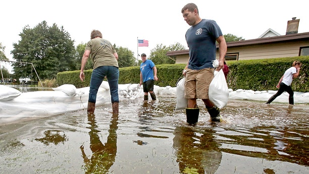 Residents layered sandbags to protect property from flooding.