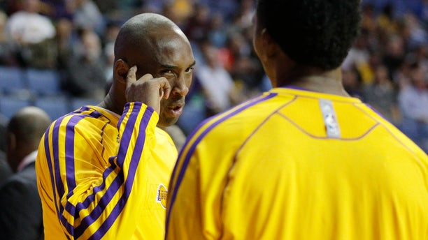 Los Angeles Lakers' Kobe Bryant, left, talks to Nick Young before an NBA preseason basketball game against the Denver Nuggets on Tuesday, Oct. 8, 2013, in Ontario, Calif. (AP Photo/Jae C. Hong)