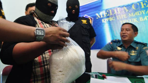 "File picture shows an unidentified suspected drugs courier (L) holding a bag containing ""crystal meth"" (methamphetamine hydrochloride) at the customs office in Padang, West Sumatra province on May 28, 2013."