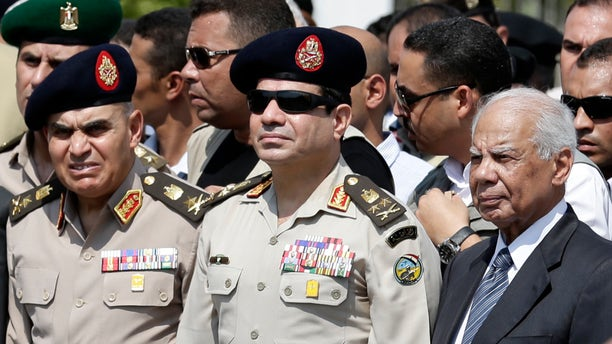 FILE - In this file photo taken Friday, Sept. 20, 2013, Egypt's Defense Minister Gen. Abdel-Fattah el-Sissi, center, Egyptian Prime Minister Hazem el-Beblawi, right, and army's Chief of Staff Lt. Gen. Sedki Sobhi, left, attend the funeral of Giza Police Gen. Nabil Farrag in Cairo, Egypt. A heavy crackdown has thrown the 85-year-old Brotherhood into an existential crisis. Once Egypt's dominant political force, it is now reduced to keeping a campaign of street protest simmering to show it cannot be completely wiped out and must one day have a place again in the political system. (AP Photo/Hassan Ammar, File)