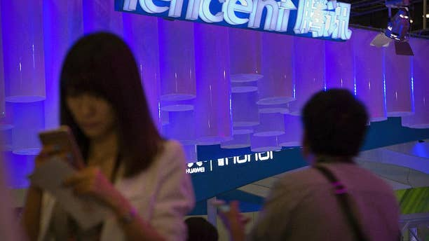 """In this April 29, 2015 photo, a woman uses her smartphone near a booth for the Chinese Internet company Tencent at the Global Mobile Internet Conference in Beijing. Chinese state media reported Thursday, Aug. 18, 2016, that new rules hold chief editors of news websites personally liable for content, months after several portals posted material that was seen as embarrassing to President Xi Jinping. Tencent, one of China's most popular websites, fired its top editor after a July headline mistakenly said Xi delivered a """"furious"""" - instead of """"important"""" - speech commemorating a Communist Party anniversary. (AP Photo/Mark Schiefelbein)"""