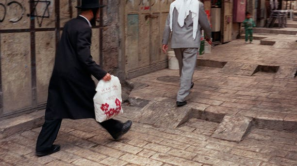 "FOR STORY ISRAEL NATION : In this June 12, 1997 file photo, an Orthodox man walks behind a Palestinian man on a street in the walled Old City of Jerusalem.  Israel's national population registry lists many ""nationalities"" and ethnicities, among them Jew, Arab, Druze and more, but one ethnicity is conspicuously absent from the list: Israeli. The Israeli Supreme Court ruled this week that residents cannot identify themselves as Israelis in the national registry because it could affect the country's Jewish character, in court documents obtained Thursday, Oct, 3, 2013. (AP Photo/Greg Marinovich, File)"