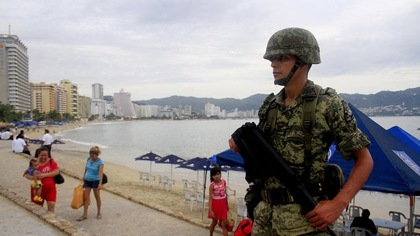 A soldier stands guard along a beach during an operation to help increase security in Acapulco, Mexico.