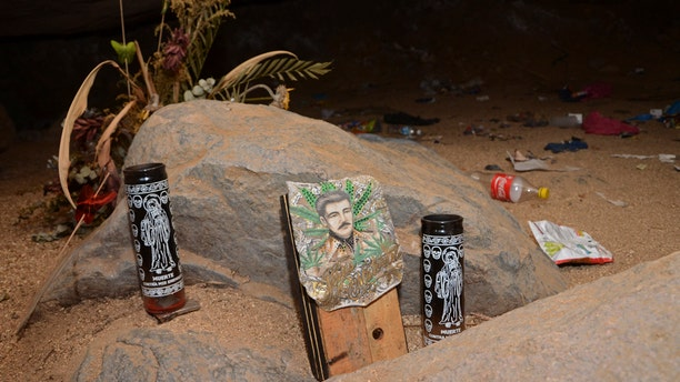 """June 8: Candles depicting the """"Santa Muerte"""" and an image of Jesus Malverde, center, stand at the entrance of a cave near the site where mass graves were found in the Pacific resort city of Acapulco, Mexico.  (AP Photo/Bernandino Hernandez)"""