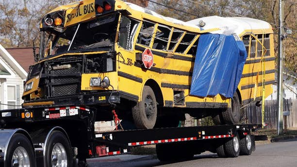 FILE - In a Tuesday, Nov. 22, 2016 file photo, a school bus is carried away, in Chattanooga, Tenn, from the site where it crashed on Monday. Attorney Amanda Dunn says she anticipates bus driver Johnthony Walker will plead not guilty if a grand jury indicts him. He's charged with five counts of vehicular homicide. Police say another count will be added. (AP Photo/Mark Humphrey, File)