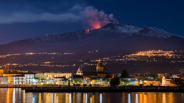 Mount Etna, Europe's most active volcano, spews lava as the Sicilian town of Riposto, Italy, is visible in foreground, during an eruption in the early hours of Tuesday, April 11, 2017