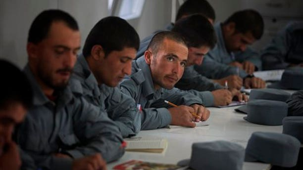 In this Nov. 7 photo, new Afghan police recruits attend a literary class at Central Training Center on the outskirts of Kabul. (AP Photo)