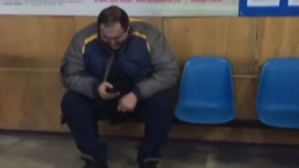 A man reacts in an airport in Orsk, Russia after a plane with 71 people on board crashed shortly after takeoff from Moscow.
