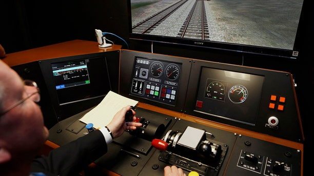 Metrolink Director of Operations, R.T. McCarthy, demonstrates Metrolink's implementation of Positive Train Control (PTC) at the Metrolink Locomotive and Cab Car Simulators training facility in Los Angeles' Union Station. Amtrak is considering suspending service on tracks that don't have sophisticated speed controls by a Dec. 31, 2018 deadline.