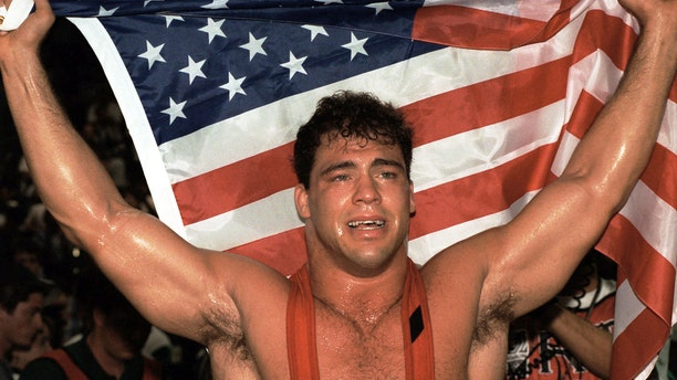 Kurt Angle of the United States celebrates his gold medal in the 100 kg class of freestyle wrestling at the Centennial Olympic Games in Atlanta Wednesday July 31, 1996.  Angle defeated Abbas Jadidi of Iran.  (AP Photo/Michel Lipchitz)