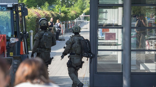 Special police guard outside  a subway station in Munich, Germany, Tuesday, June 13, 2017.  Several people were injured, including a police officer, in a shooting early Tuesday at a Munich subway station, police said. Munich police said in a tweet that the policewoman's injuries were serious. The suspect was also injured and is in custody. The shooting occurred during a morning police check at the Unterfoehring subway station, Munich police spokesman Michael Riehlein said. (Andreas Prott/dpa via AP)