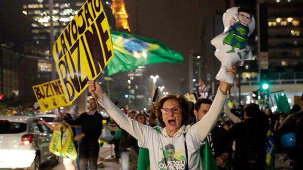 Demonstrators celebrate the decision by Judge Sergio Moro to convict former Brazilian President Luiz Inacio Lula da Silva in Sao Paulo, Brazil, Wednesday, July 12, 2017. Silva was found guilty of corruption and money laundering Wednesday and sentenced to almost 10 years in prison. (AP Photo/Andre Penner)
