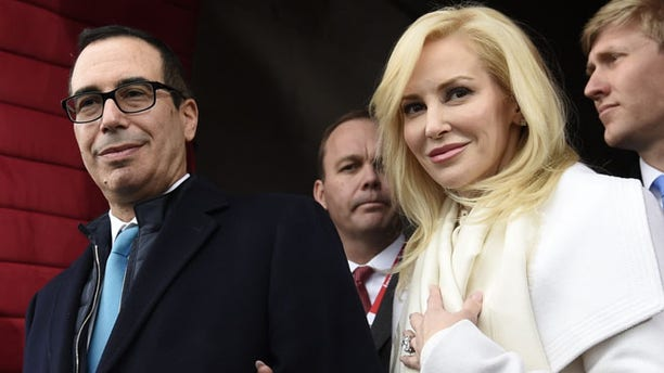 "FILE - In this Friday, Jan. 20, 2017, file photo, then Treasury Secretary-designate Stephen Mnuchin and his then-fiancee, Louise Linton, arrive on Capitol Hill in Washington, for the presidential inauguration of Donald Trump. Linton responded to a social media critic on Aug. 21, 2017, telling the mother of three that that she was ""adorably out of touch."" Mnuchin and Linton were married in June. (Saul Loeb/Pool Photo via AP, File)"