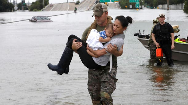 Houston Police SWAT officer Daryl Hudeck carries Catherine Pham and her 13-month-old son Aiden after rescuing them from their home surrounded by floodwaters from Tropical Storm Harvey Sunday