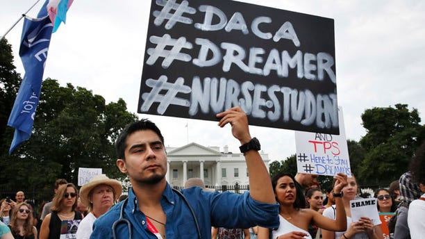 Carlos Esteban, a student from Virginia, with pro-DACA activists outside the White House in September.
