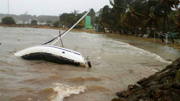 A boat lays on its side off the shore of Sainte-Anne on the French Caribbean island of Guadeloupe, early Tuesday, Sept. 19, 2017, after the passing of Hurricane Maria.