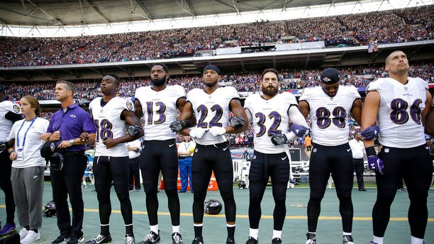 Baltimore Ravens head coach John Harbaugh stands with his arms locked with his daughter and players during the playing of the National Anthem before their game against the Jacksonville Jaguars in London.