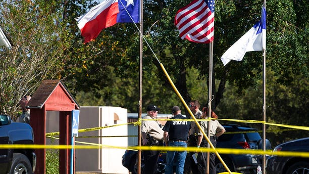 Law enforcement officials stand next to a covered body at the scene of a fatal shooting at the First Baptist Church in Sutherland Springs, Texas, on Sunday, Nov. 5, 2017.