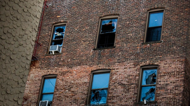 This photo shows broken windows on the back of the building where more than a dozen people died late last month. A fire broke out when a young boy played with the burners on his mother's stove, officials said.