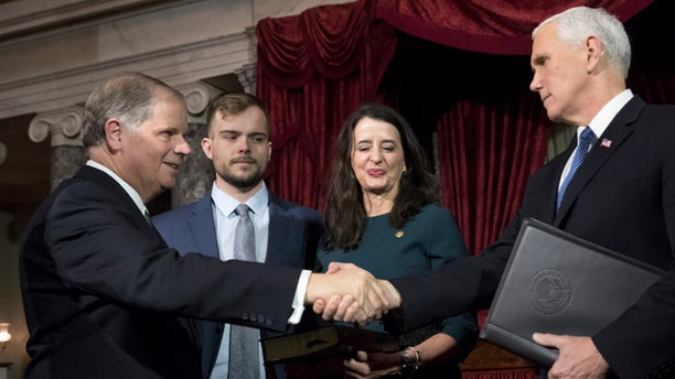 Vice President Mike Pence, right, shakes hands with Sen. Doug Jones, D-Ala., left, after administering the Senate oath of office during a mock swearing in ceremony in the Old Senate Chamber to Jones, with his wife Louise Jones, second from right, Wednesday, Jan. 3, 2018 on Capitol Hill in Washington.