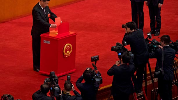 Chinese journalists film President Xi Jinping casting his ballot during a plenary session of China's National People's Congress at the Great Hall of the People in Beijing.