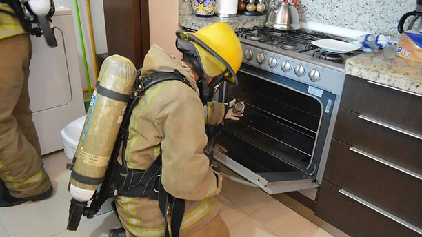 A firefighter is seen examining a gas stove in the rented condo where an Iowa couple and their two children died in Tulum, Mexico.