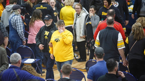 Beth and Rodger Fry, center, are seen leaving the service held for their daughter Amy Sharp and her family on Saturday in Creston, Iowa.