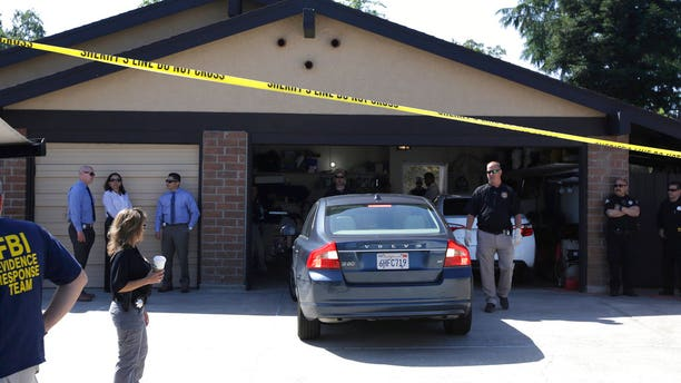 A car is backed out of the garage of a home searched in connection with the arrest of a man on suspicion of murder, Wednesday, April 25, 2018, in Citrus Heights, Calif.