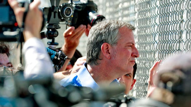 New York City Mayor Bill de Blasio looks through a closed gate at the Port of Entry facility, in Fabens, Texas, where tent shelters are being used to house separated family members..