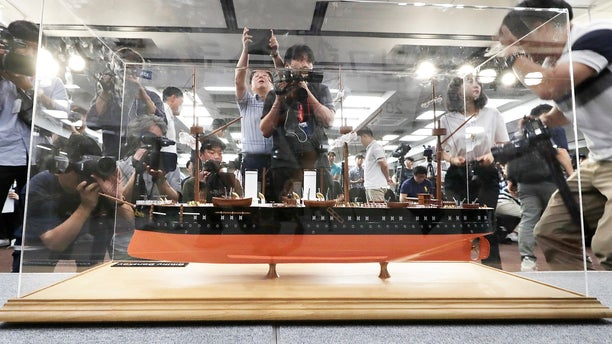 In this July 26, 2018 photo, a scale model of the Russian warship Dmitrii Donskoi is surrounded by the media before a news conference in Seoul, South Korea.