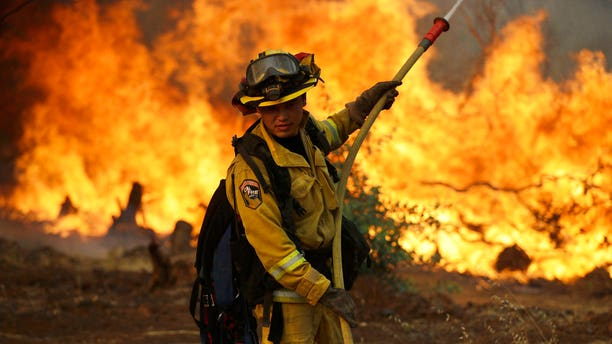 A firefighter makes a stand in front of an advancing wildfire as it approaches a residence Saturday, July 28, 2018, in Redding, California.