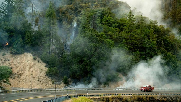 A fire truck passes a smoldering hillside as the Carr Fire burns along Highway 299 in unincorporated Shasta County, California, on Saturday, July 28, 2018.