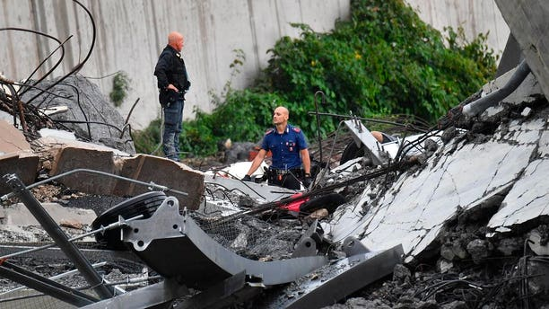 Rescues work among the debris of the collapsed Morandi highway bridge in Genoa.