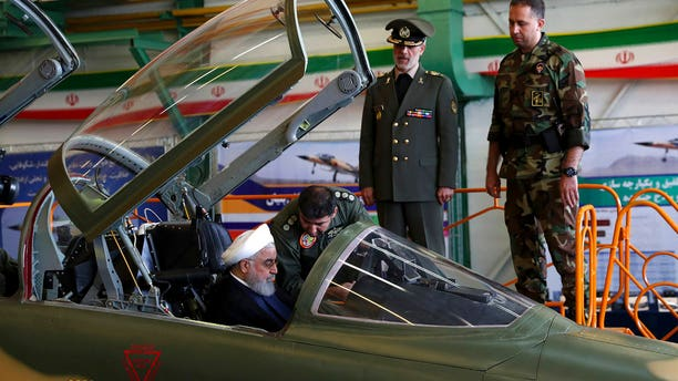 Iranian President Hassan Rouhani is briefed by an air force pilot as he sits in the cockpit of a fighter jet on Tuesday
