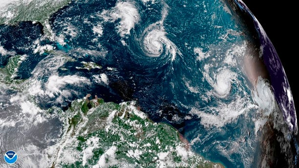 An enhanced satellite image made available by NOAA shows Tropical Storm Florence, center, in the Atlantic Ocean on Saturday.