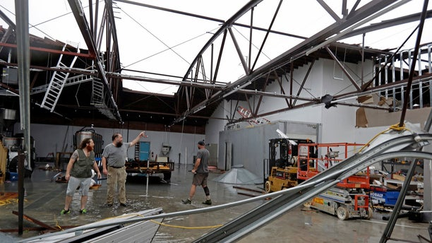 Ethan Hall, right, Michael Jenkins, center, and Nash Fralick, left, examine damage to Tidewater Brewing Co. in Wilmington, N.C., after Hurricane Florence made landfall.