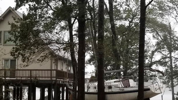 This photo provided by Angie Propst, shows a boat wedged in trees during Hurricane Florence in Oriental, North Carolina.