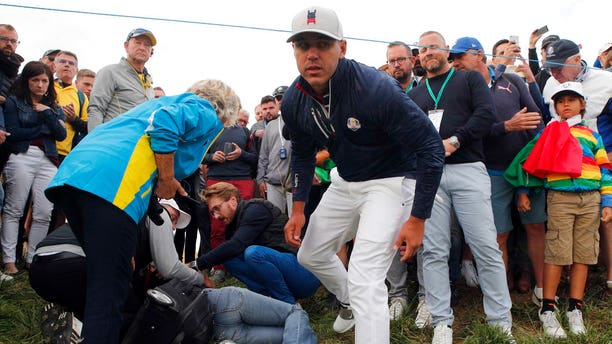 Brooks Koepka stares into the camera after checking on a fan who he hit with an errant tee drive at The Ryder Cup